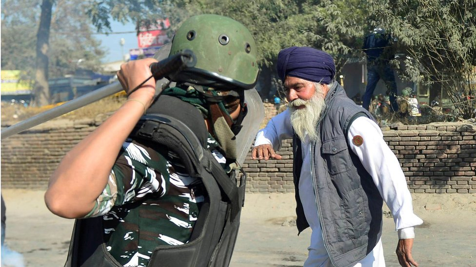 A police officer raises his baton to hit a farmer