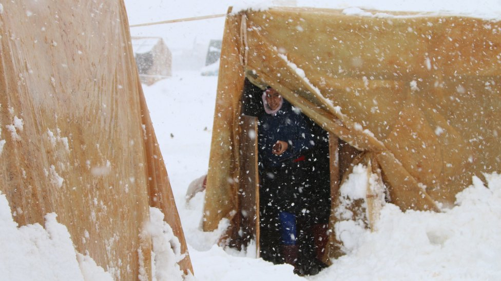 A Syrian refugee stands at the entrance of a tent during a snowstorm at camp in Lebanon