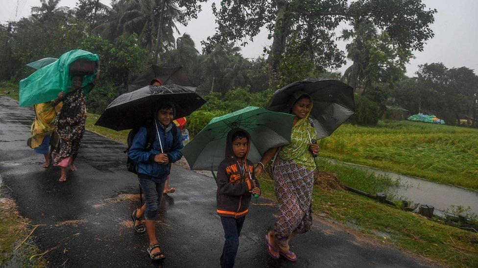 Villagers holding umbrellas carry their belongings on their way to enter a relief centre in India