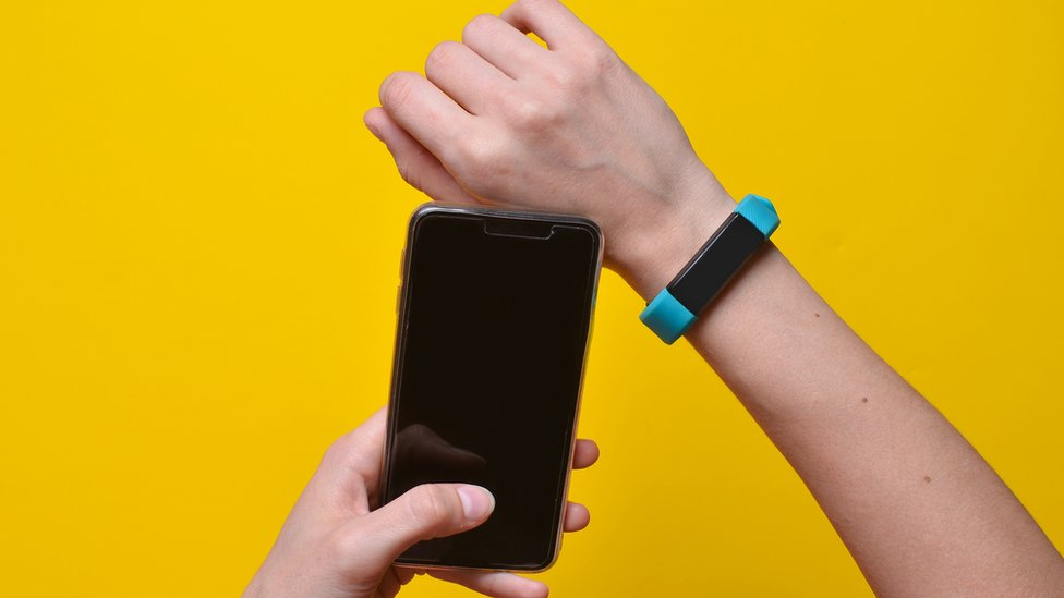 Person holding a smartphone and wearing a linked device on their wrist