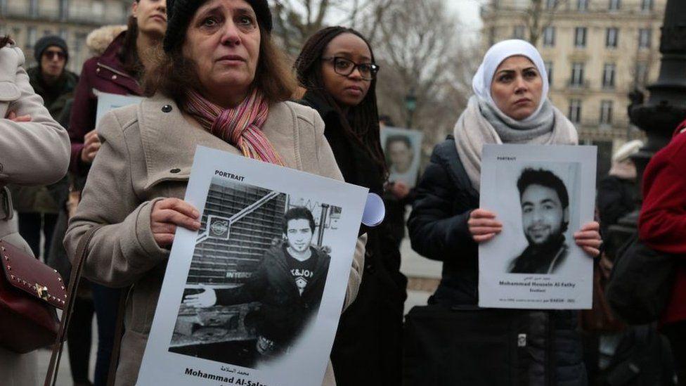 أقارب ضحايا يحملون صورهم
