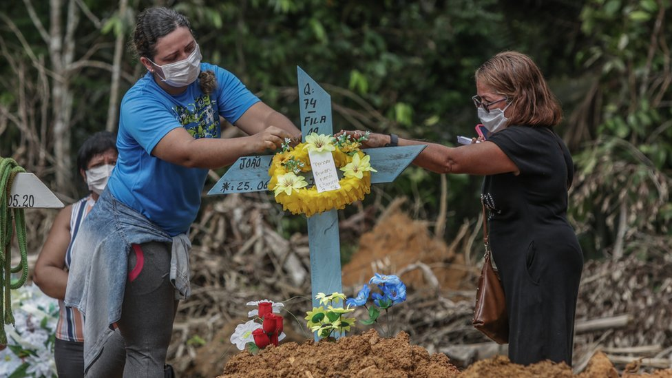 Women put flowers after the burial of a man in Manaus