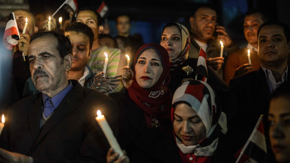 Egyptians hold candles at a vigil outside the Syndicate of Journalists in Cairo on 27 November 2017