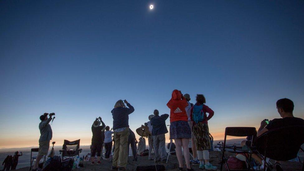 Eclipse solar total y personas mirándolo.