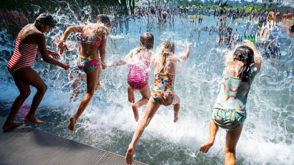 Niños refrescándose en una fuente de Richmond, Columbia Británica, 29 de junio de 2021