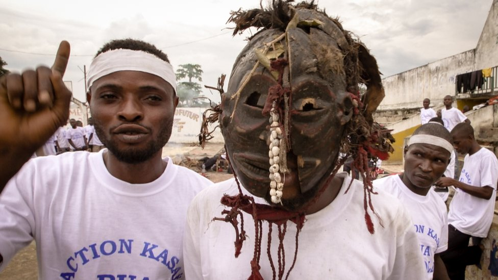 Two young fighters in Kananga town - one wears a traditional mask used in witchcraft ceremonies.
