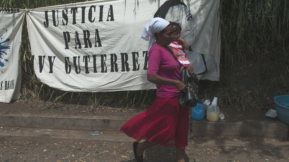 BBC, NO USAR |  Una mujer y su hija pasan delante de un cartel en julio de 2018, en Sonsonate, en contra de las detenciones ilegales.