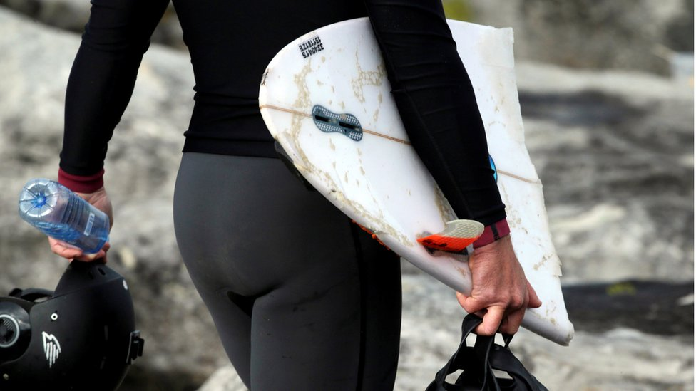a person in a wetsuit carrying part of a broken surfboard