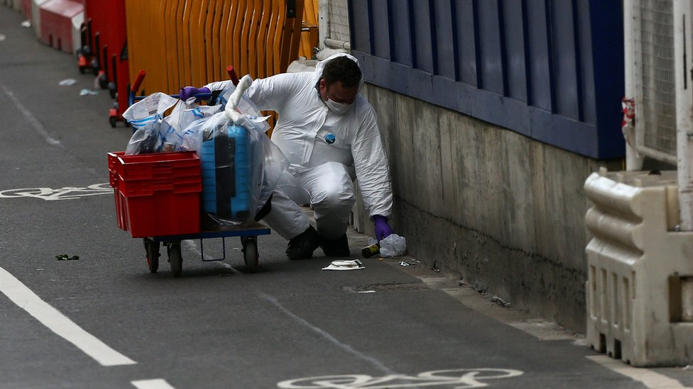 Forensics officers collect evidence at the scene