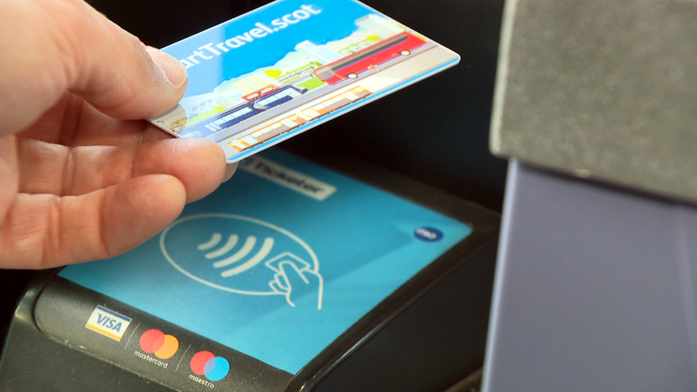 A close up of someone using a smartcard on a bus