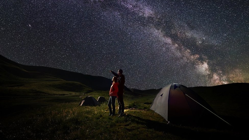A father and a child, camping, admiring the starry night sky