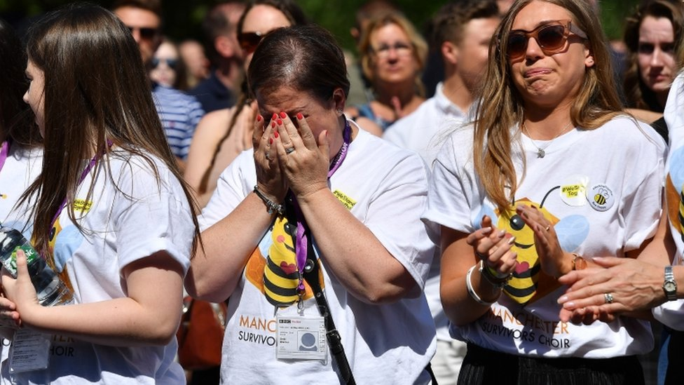 A woman cries outside Manchester Cathedral
