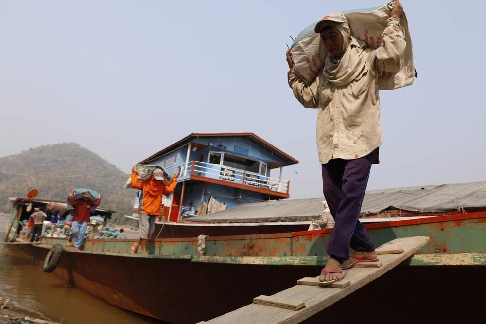 船隻停泊在琅勃拉邦的東邁(Don Mai)港,老撾工人從船上搬運一袋袋大米。