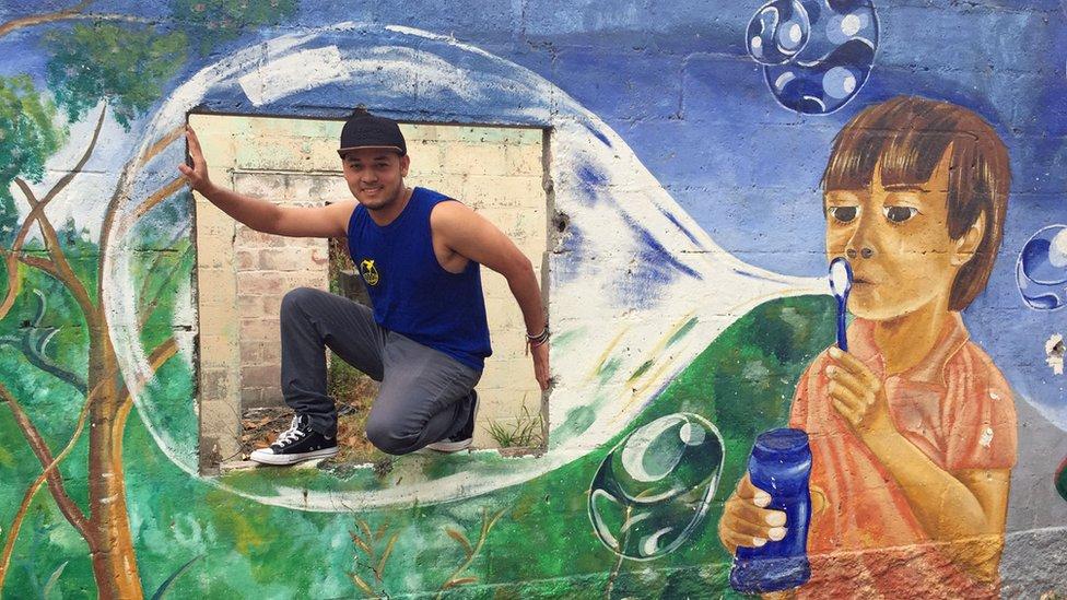 Kelvin en un mural pintado por su grupo.