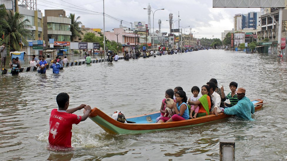People travel on a boat as they move to safer places through a flooded road in Chennai