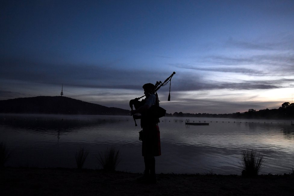 A bagpipe player plays at the Winter Solstice Nude Charity Swim in Canberra
