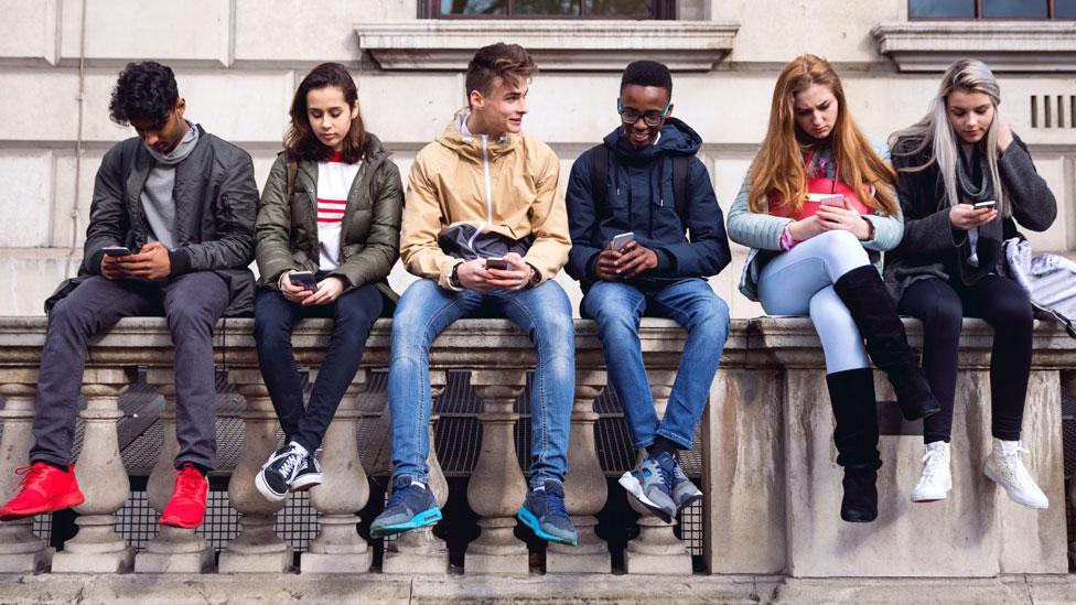 Teenagers using mobile phones