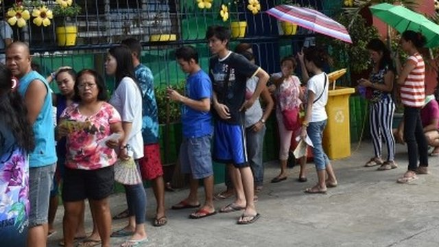Voters queue to cast their ballots in Manila
