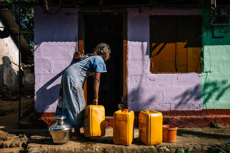 A woman collects water in containers outside her house