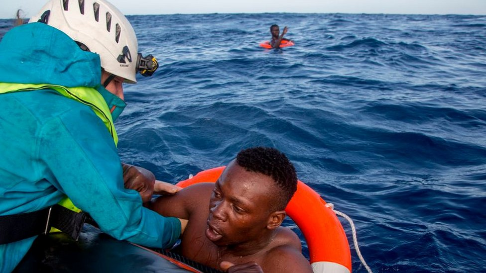 Rescue worker pulling migrant out of sea