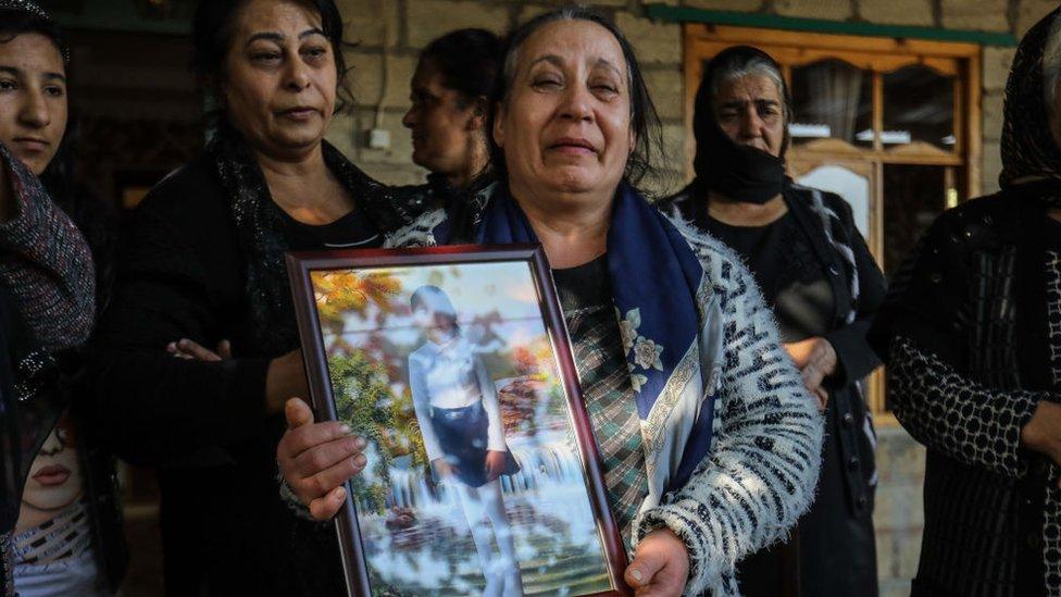 Mujeres sostienen el retrato de una niña matada por el ejército armano