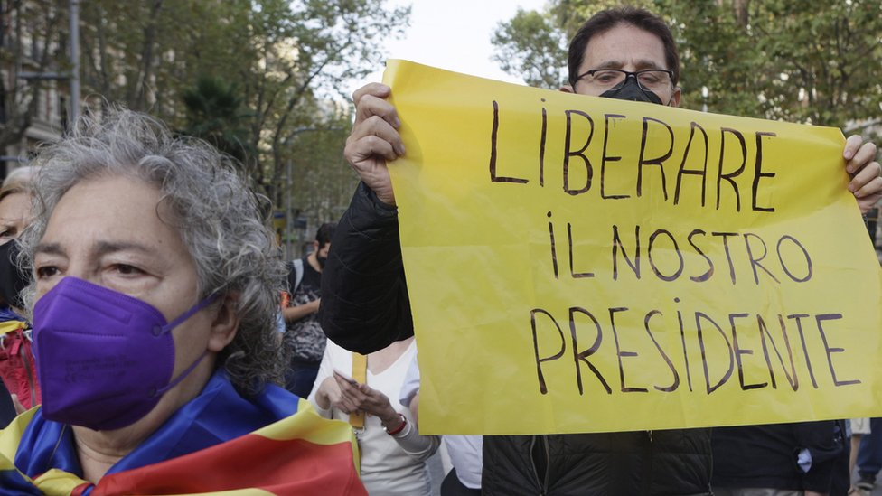 """A demonstrator holds a banner reading in Italian language """"Free Our President"""" as several dozens people rally in front of Italian Consulate"""