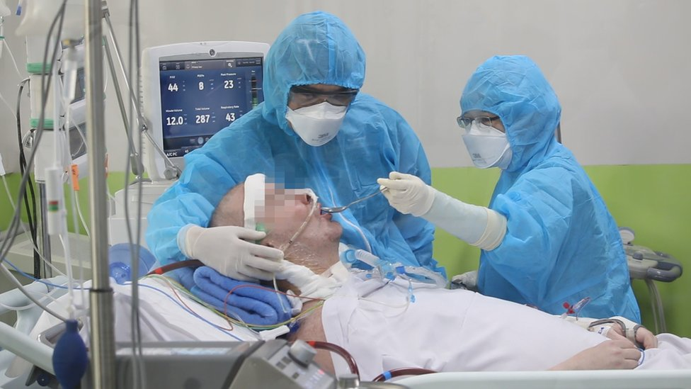 Stephen Cameron, face blurred, is fed by masked staff in a hospital bed