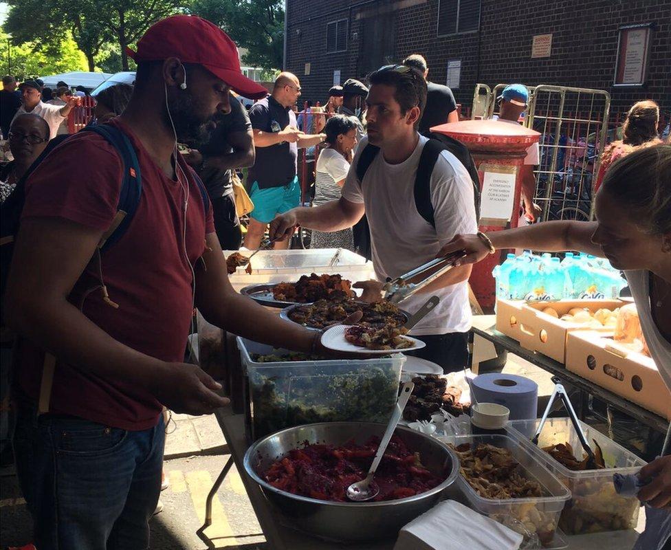 Volunteers serve food to people near Grenfell Tower