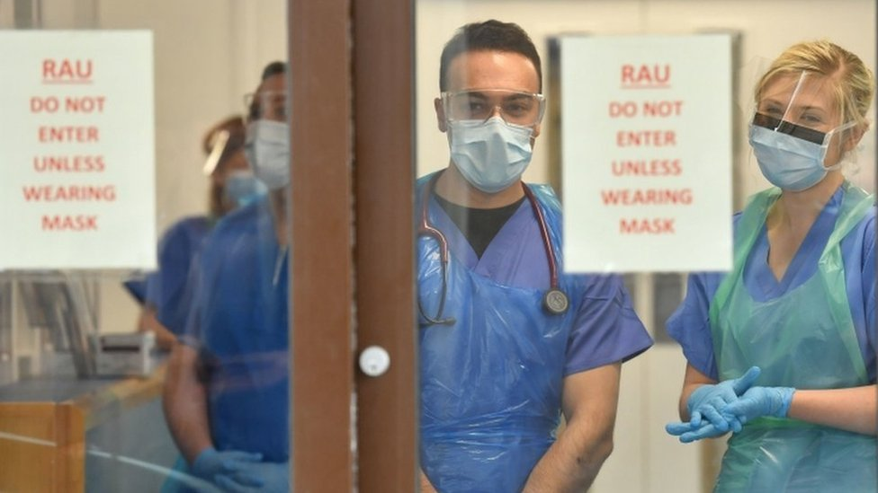Medical staff wearing personal protective equipment (PPE) wait to receive coronavirus patients at the door of the Respiratory Assessment Unit at the Morriston Hospital in Swansea
