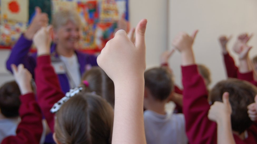Pupil making thumbs up sign