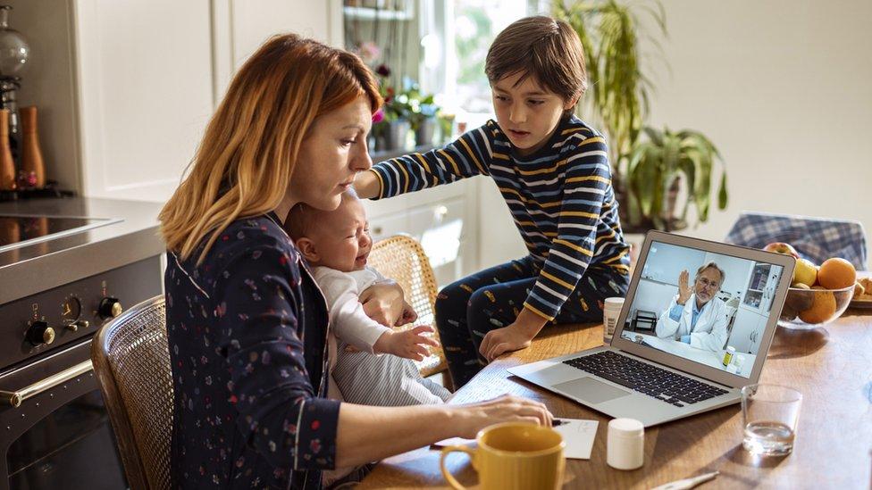 Madre trabajando y cuidando de sus niños al mismo tiempo.
