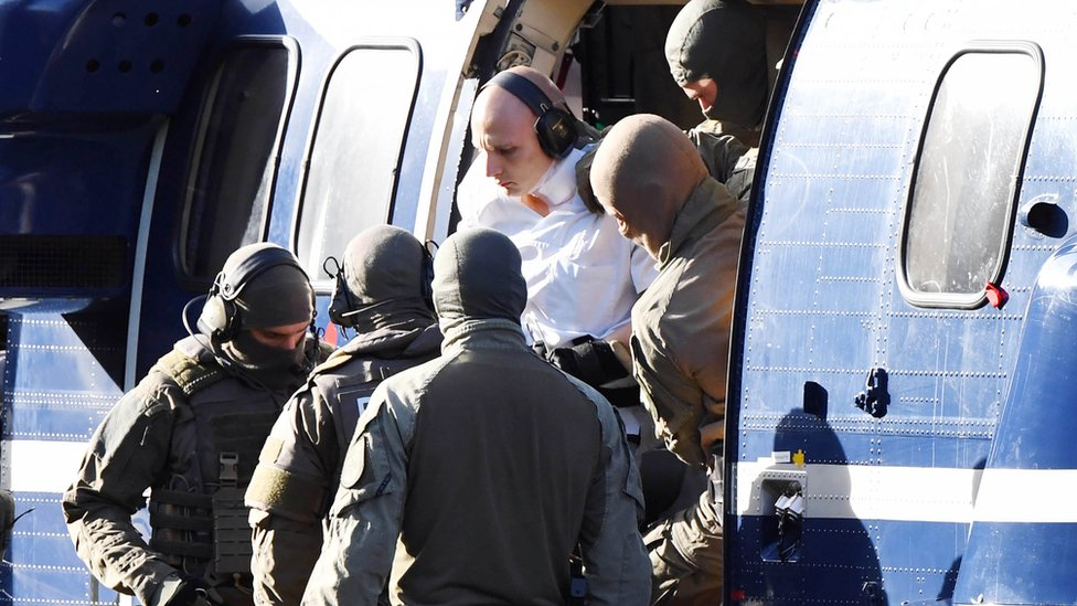 A person believed to be the suspect in the Halle shooting is assisted by policemen to get out of a helicopter after it landed at the Federal Supreme Court (Bundesgerichtshof) in Karlsruhe, southern Germany, on October 10, 2019