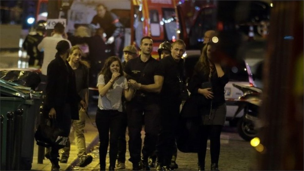Rescuers evacuate people following an attack in the 10th arrondissement of the French capital Paris