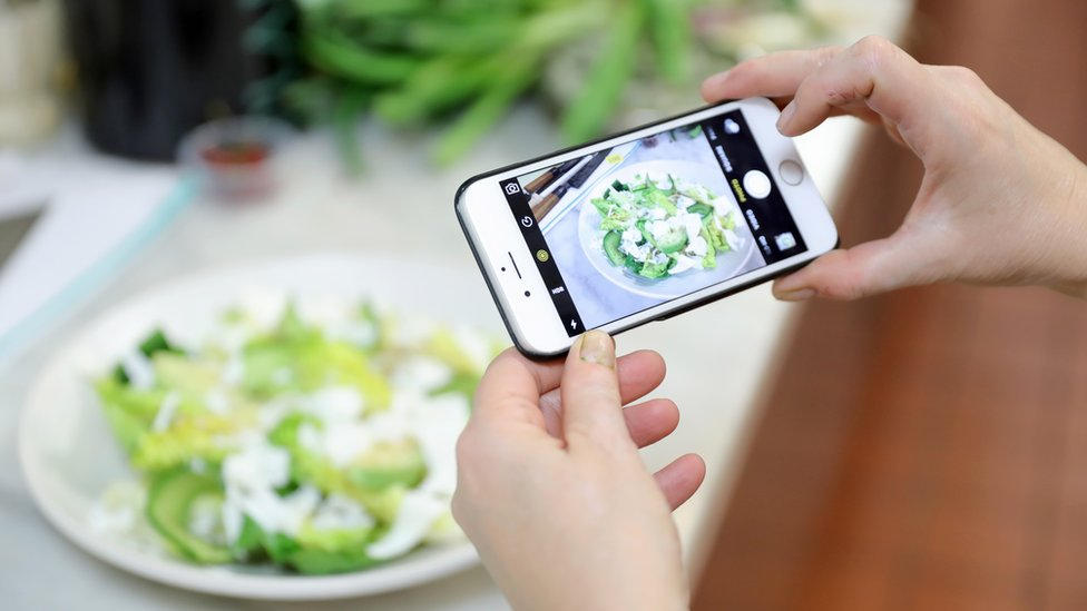 Woman with an Iphone takes picture of an avocado salad