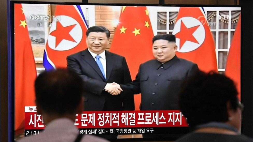 People watch a television news screen showing North Korean leader Kim Jong Un shaking hands with Chinese President Xi Jinping