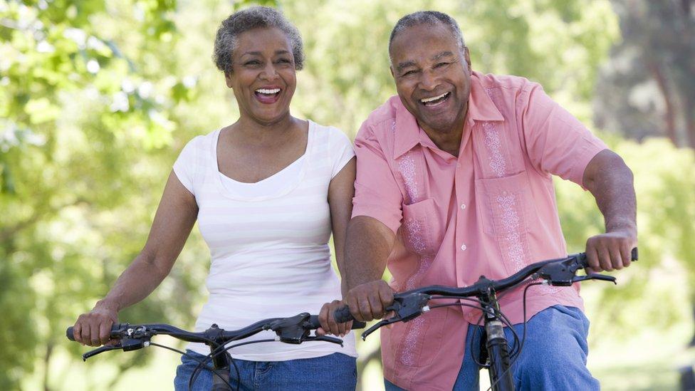 Pareja de edad montando en bicicleta