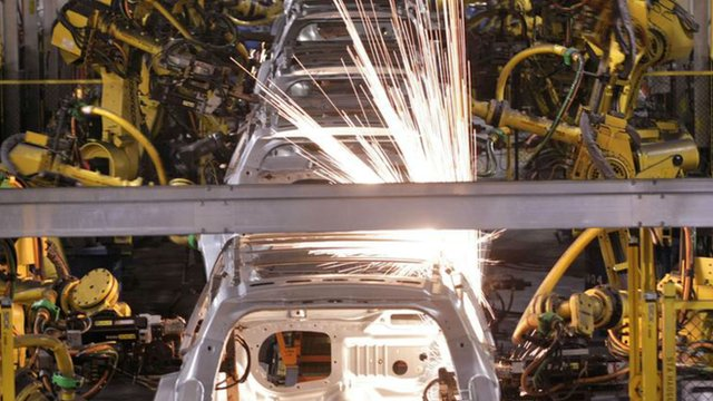 Robot arms welding cars