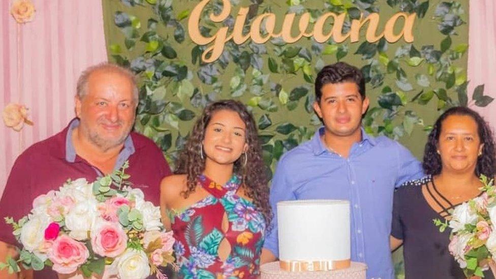 Pais de Giovana e a jovem em foto antiga, tirada em frente a uma mesa de festa
