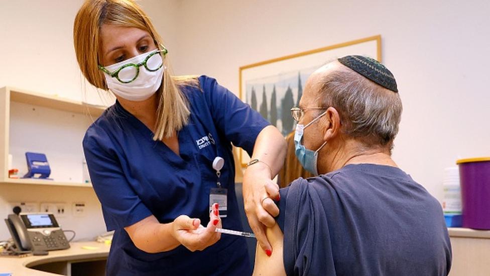 Profissional da saúde aplica vacina no braço de um homem