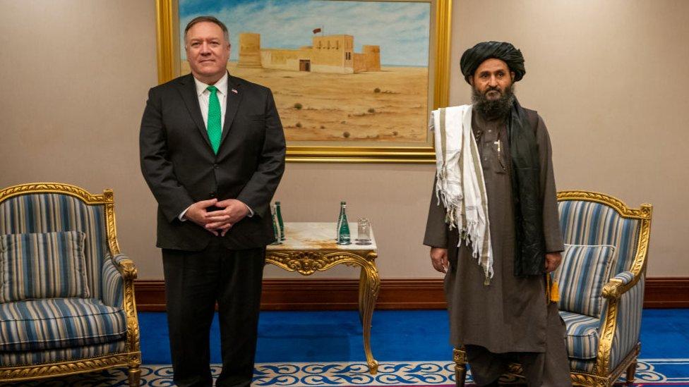 Mike Pompeo, ex secretario de Estado de EE.UU., junto al jefe de asuntos políticos del Talibán, Mullah Abdul Ghani Baradar, en Doha en 2020.