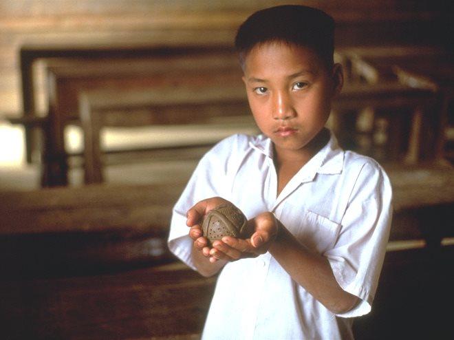 Un niño de Laos muestra una bomba de racimo