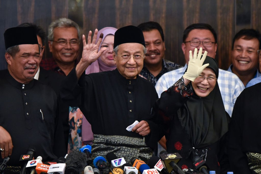 Prime Minister Mahatir Mohamad waves to the crowd at a press conference