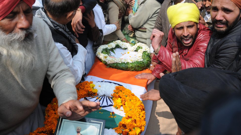 Relatives of Central Reserve Police Force soldier Sukhjinder Singh mourn near his coffin before his cremation ceremony at village Gandiwind in Tarn Taran district