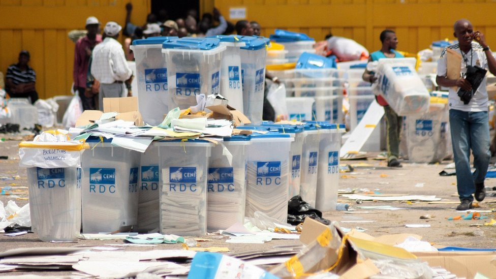 Electoral agents of the National Independent Electoral Commission (CENI) alongside ballot boxes in the Democratic Republic of Congo, 2 December, 2011