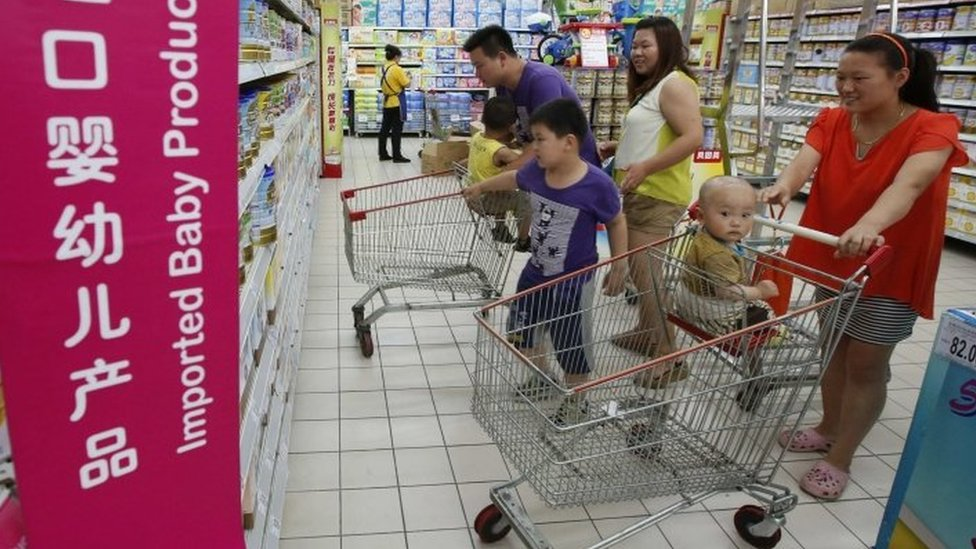 A family looks at imported milk powder products at a supermarket in Beijing in this July 3, 2013 file photo.