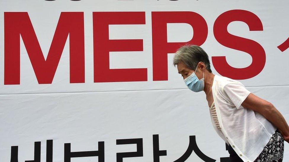 Coreano frente a letrero de MERS