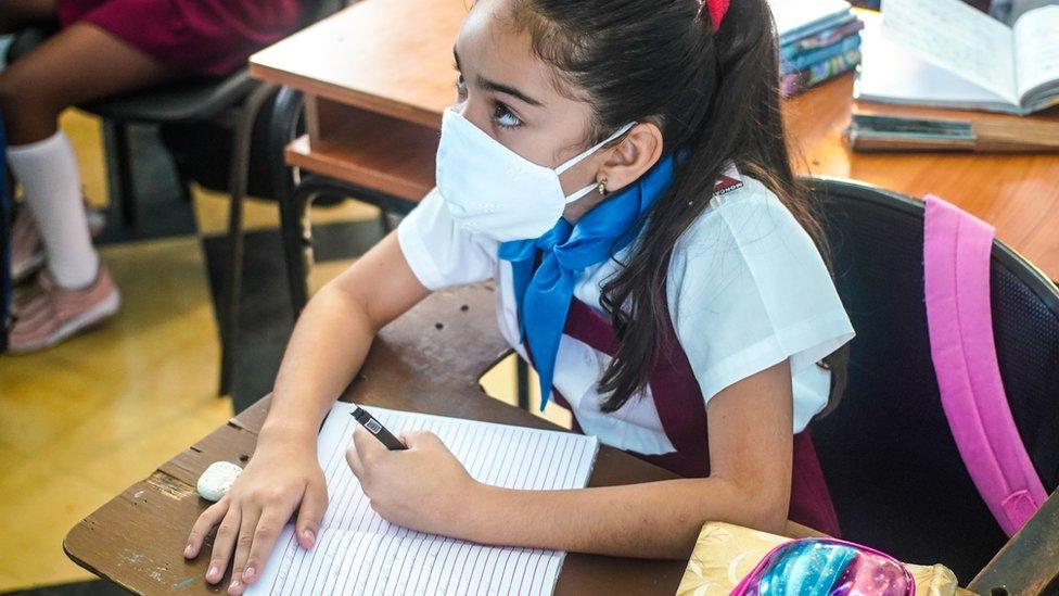Niña con mascarilla sentada en un pupitre en una escuela en Cuba