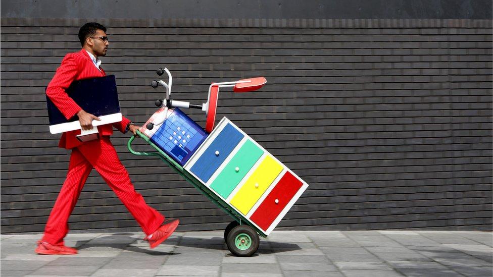 Imagen que muestra a un hombre llevando un archivador y una silla sen una carretilla.