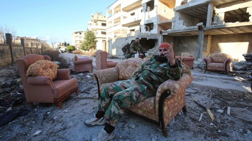 A member of the Syrian pro-government forces sits on an armchair in the strategic town of Salma, in the coastal province of Latakia (15 January 2016)