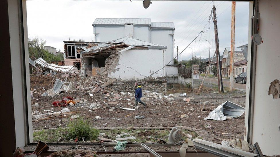 رجل يسير أمام منزل دمره القصف في ستيباناكيرت عاصمة منطقة ناغورنو كاراباخ